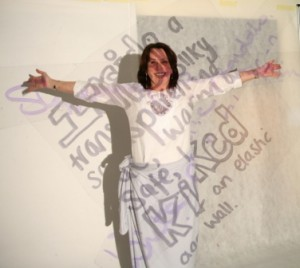 woman in white against white screen with poetry projected over her body