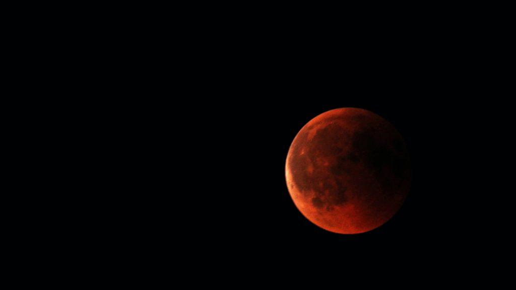 Image of full red moon in dark sky